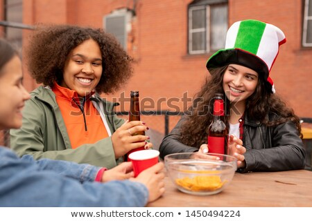 Group of happy girls with beer discussing last football match Stock photo © pressmaster