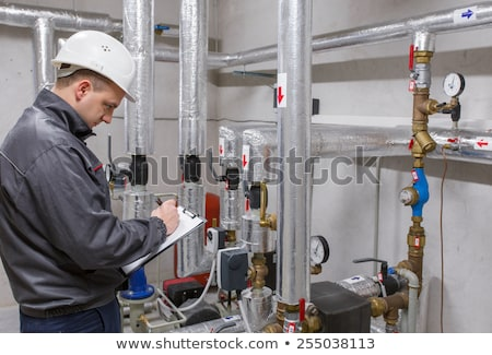 Technician inspecting heating system in boiler room Stock photo © Lopolo