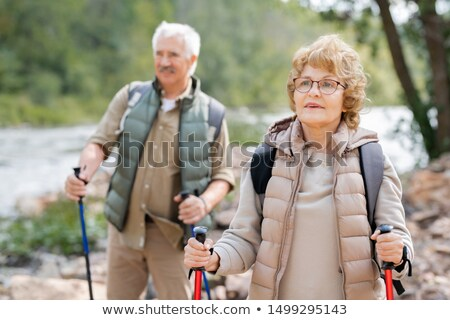 Pretty mature female hiker and her husband moving down river bank Stock photo © pressmaster
