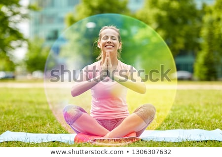 happy woman meditating in summer park over aura Stock photo © dolgachov