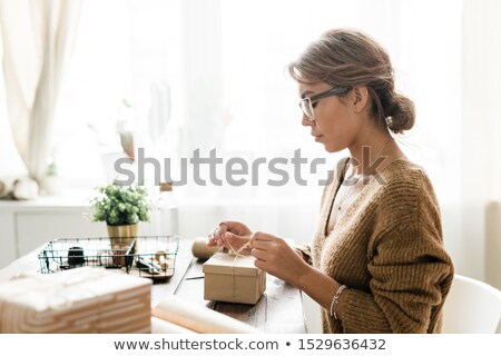 Young woman in casualwear sitting by table and binding knot on top of giftbox Stock photo © pressmaster