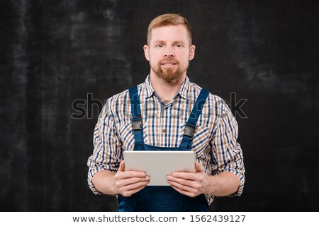 Young bearded technician in checkered shirt and blue overalls looking at you Stock photo © pressmaster