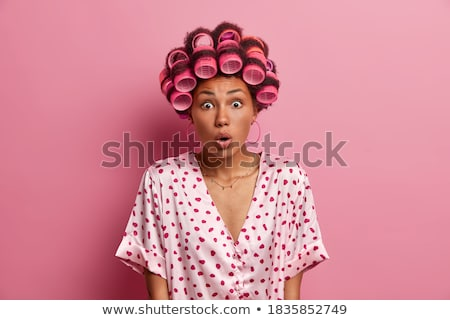 Stunned beautiful curly young woman looks with bated breath at camera, stares at camera, wears red s Stock photo © vkstudio