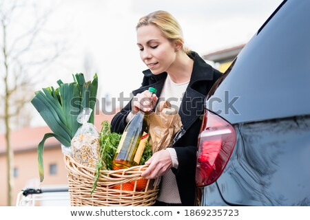 Woman storing basket with groceries into trunk after shopping Stock photo © Kzenon