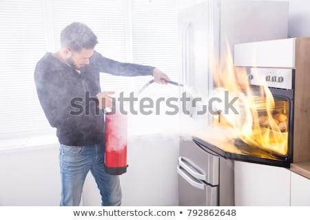 Férfi tűzoltó készülék sütő konyha tűz otthon Stock fotó © AndreyPopov