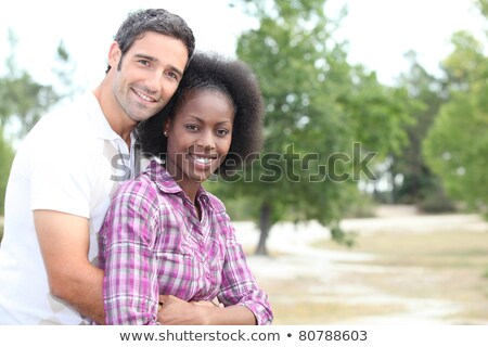 Mixed race couple cuddling in the countryside Stock photo © photography33