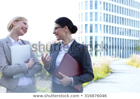Businesswoman holding a file folder and a laptop Stock photo © photography33