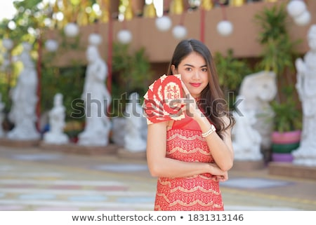 Beautiful woman wearing traditional Asian clothing with a fan stock photo © wavebreak_media