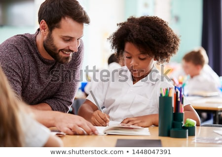 two male primary school pupils and teacher working at desk in cl stock photo © monkey_business
