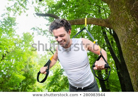 People in park on suspension or sling trainer Stock photo © Kzenon