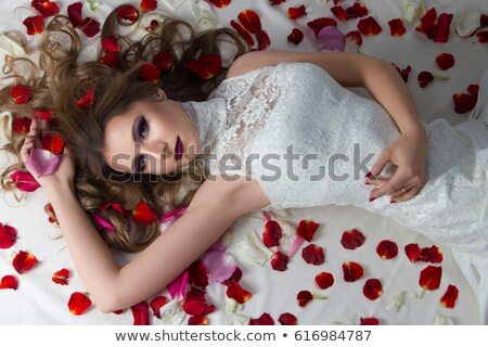 beautiful bride on floor among red rose petals stock photo © fanfo