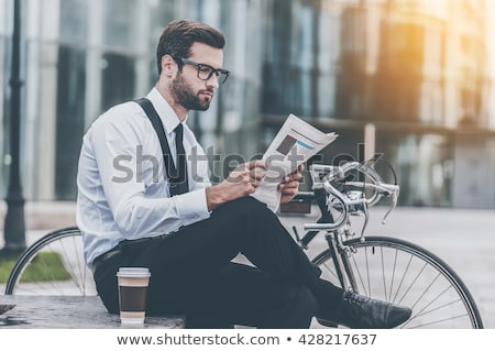 young businessman reading a newspaper outdoors stock photo © deandrobot