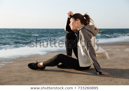 photo of charming sport woman sitting on the beach wipes the swe stock photo © deandrobot