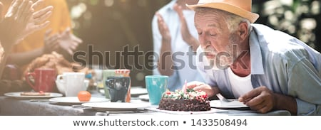 couple lighting candles on cake for son stock photo © is2