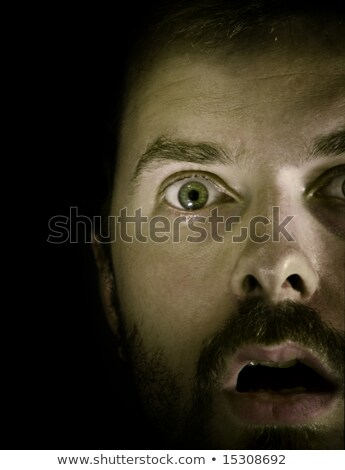Close up portrait of a frightened young bearded man Stock photo © deandrobot