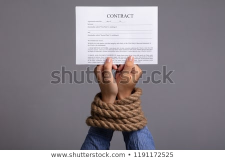 Woman's Hand Tied With Rope Holding Contract Form Stock photo © AndreyPopov