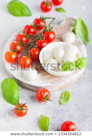 Fresh Mini Mozzarella cheese on vintage chopping board with tomatoes and basil leaf on stone kitchen Stock photo © DenisMArt