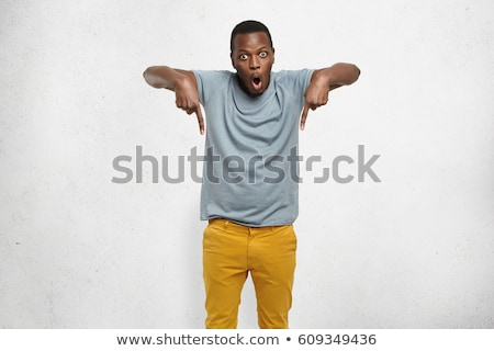 Portrait of stylish african american guy smiling and pointing fi Stock photo © deandrobot