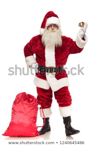 saint nick holding bell stands near presents bag Stock photo © feedough