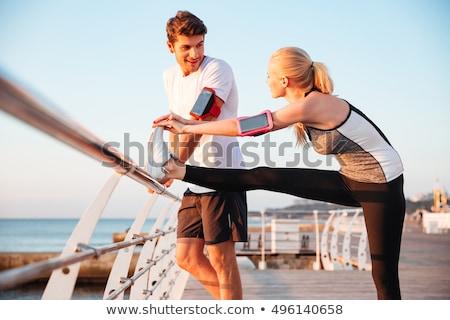 happy couple warming up on pier before training Stock photo © dolgachov