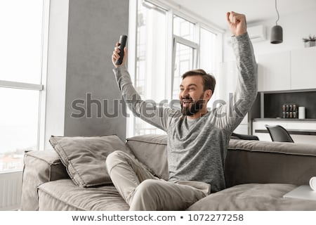 Portrait of a cheerful young man holding TV remote control Stock photo © deandrobot