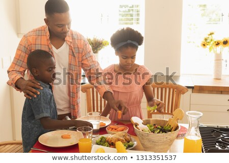 Front view of African American family having food at dining table in a comfortable home Stock photo © wavebreak_media