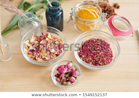 Group of bowls with dry rose petals and small jar with orange slices on table Stock photo © pressmaster