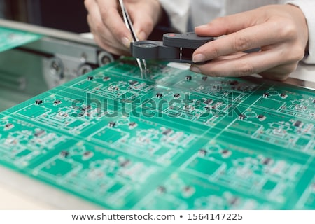 Technician inserting electronic components into a PDB for assembly Stock photo © Kzenon
