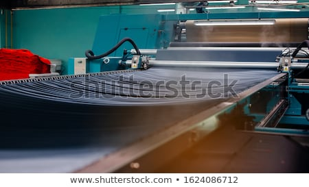 Stock photo: Textile Manufacturing. Knitted fabric. Textile factory in spinning production line and a rotating ma
