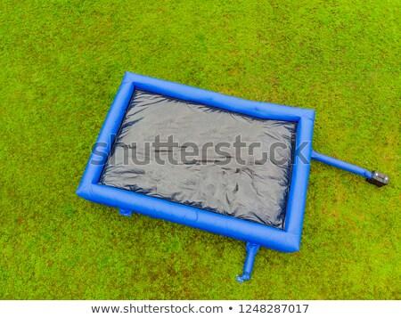 Grande inflável azul trampolim grama verde céu Foto stock © galitskaya