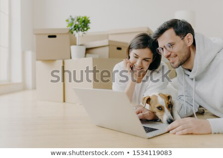 Glad young female and male discuss home repair projects, look attentively into laptop, their dog lie Stock photo © vkstudio