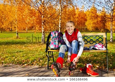 Beautiful girl ties roller skates on park bench Stock photo © darrinhenry