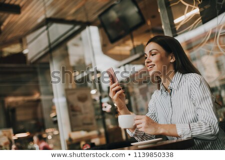 Dark-haired woman smiling on cellphone Stock photo © photography33