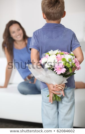 little boy hiding a bunch of flowers in his back stock photo © photography33