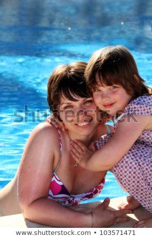 Happy family beside the swimming pool Stock photo © wavebreak_media
