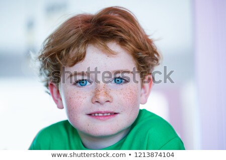 smiling young boy with green eyes Stock photo © meinzahn