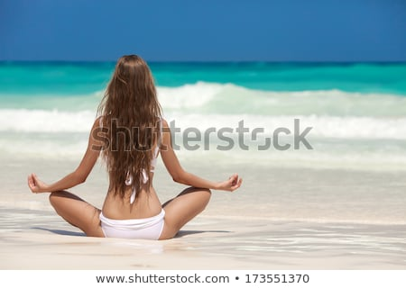 blond girl meditating on the beach stock photo © nejron