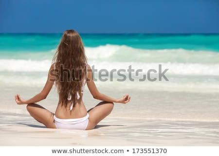 blond girl meditating on the beach stock photo © nejron