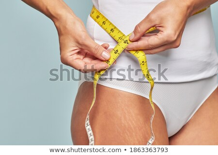 Athletic woman measuring perfect shape of beautiful thigh Stock photo © vlad_star