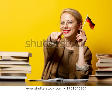 Young woman sitting at the table with German flag Stock photo © deandrobot