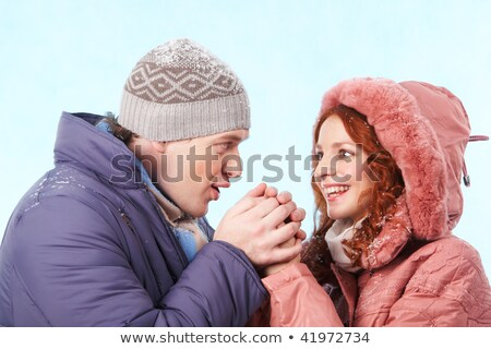 Careful man warming his girlfriend hands in winter Stock photo © deandrobot