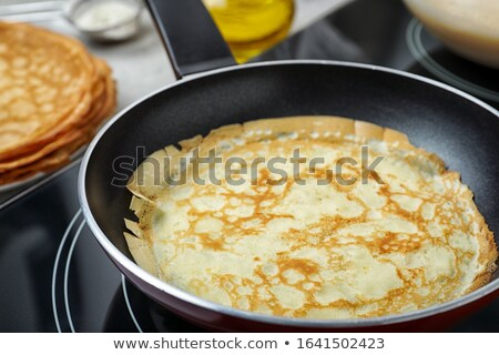Stove with pancake on pan Stock photo © deandrobot