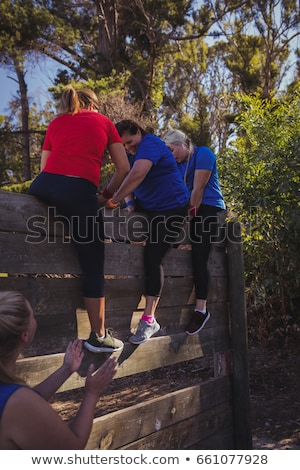 Woman being assisted by her teammates to climb a wooden wall during obstacle course training Stock photo © wavebreak_media