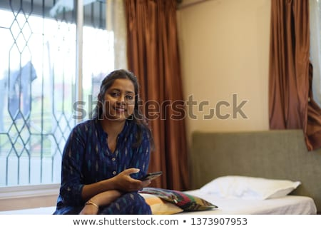 pretty indian brunette in bed smiling white sheets stock photo © iordani