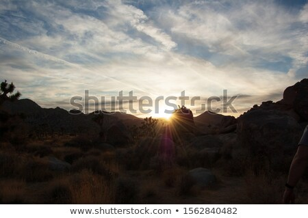 Sun setting sunburst behind mountain with blue sky and clouds ti Stock photo © lovleah