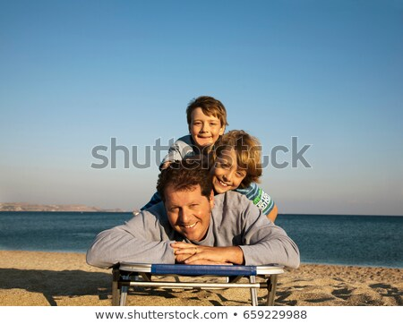 dad and two boys on sun lounger stock photo © is2