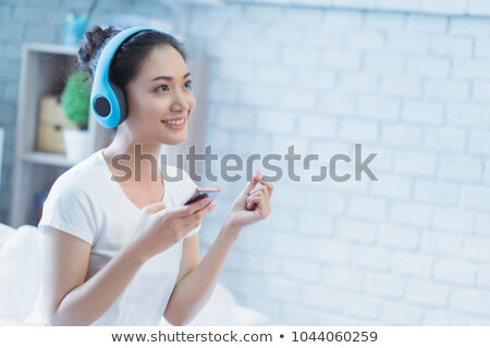 Portrait of a smiling asian girl in earphones Stock photo © deandrobot