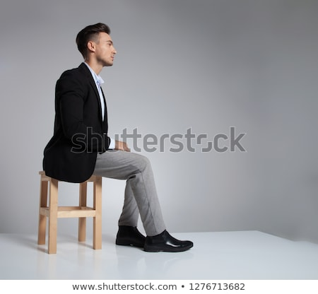 handsome businessman relaxing on wooden chair while holding hand Stock photo © feedough