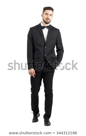 serious man wearing tuxedo and standing with hands in pockets stock photo © feedough