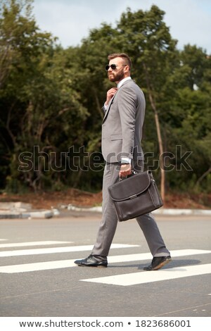 side view of handsome businessman holding suitcase walking stock photo © feedough